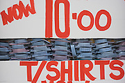 Sale price of £10 Pounds for t-shirts with shirts in window of city menswear clothes shop.