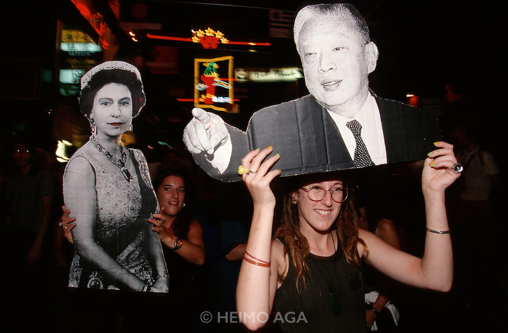 Handover Night. (Mainly Western) youth celebrating in Lan Kwai Fong, carrying images of Queen Elisabeth and Chief Executive Tung Chee-Hwa.