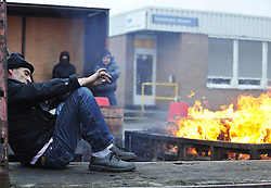 A worker rests near flame during a protest at the entrance of the Ford Genk assembly factory, in Genk of Belgium, Jan. 9, 2013, the first day to resume the production in 2013. A thin majority of workers voted to re-start to work for 40 more days in 2013 in an agreement between the direction and unions earlier in the week, but some others decided to block all access to the plant in protest. Ford Europe announced on October 24, 2012 to close its Genk plant at the end of 2014, threatening 4,300 jobs as slumping demand across Europe leaves companies with too much capacity, Brussels, Belgium, January 9, 2013. Photo by Imago / i-Images...UK ONLY