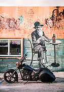 A matte black motorcycle and a Walt Whitmanesque mural at The Wynwood Brewing Company in Miami