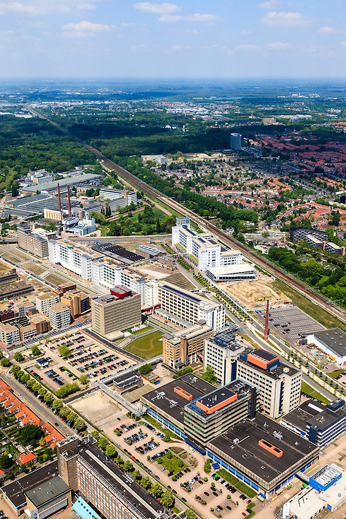 Nederland, Noord-Brabant, Eindhoven, 27-05-2013; Strijp-S, voormalige Philipsterrein, was niet toegankelijk voor het publiek, 'de verboden stad'. Het gebied, met diverse Rijksmonumenten, wordt ontwikkeld voor wonen, werken en cultuur.<br /> Rechts naast spoorlijn Philitefabriek met Klokgebouw (Strijp S), in het midden het Veemgebouw en De Hoge (Witte) Rug. <br /> <br /> Strijp-S, former Philips area, was not accessible to the public, 'the forbidden city'. The area, with several national monuments, is designated for living, working and culture.<br /> Next to railroad Philitefabriek / Clock Building (Strijp S), in the middle of the Veemgebouw and the High (White) Back. <br /> <br /> luchtfoto (toeslag op standard tarieven);<br /> aerial photo (additional fee required);<br /> copyright foto/photo Siebe Swart