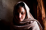 Afghanistan: 15 year old Marja waits near a cook pot of food in the doorway of the home she shares with her mother and 5 siblings...Bibi Marjan, a 30-40 year old mother of 6. A returnee from Iran in 2002, she says she and her husband fled the fighting in Kabul in 1993. She now lives alone with her children after her husband, an unskilled labourer, developed a chronic chest complaint that limits his movement, he lives with his sister on the outskirts of the city...The only income the family has, is obtained from begging in her blue burqa and sending 2 of her sons out to wash cars in Kabul city. Her 2 youngest boys occasionally attend the local school. Her eldest child, 15 year old daughter named Marja no longer goes to school as Bibi Marjan fears she will be kidnapped for marriage on her way to or from school. She says she's had many offers of money and marriage proposals for her daughter in recent months...Two of her sons, Roman (11) and Negmar (10) travel into the city daily to wash cars for 40 Afs (US$1) per car. They say they get on average 2 cars per day. During winter months when the weather is coldest they will work the shared taxis and buses touting for customers and shared rides, for this they will sometimes be paid 5 Afs by the driver depending on how many customers they attract...Although Bibi Marjan admits 40-80 Afs is not enough to feed her family on a daily basis, she believes God will give them all they need...Afghans returning from exile abroad face many challenges. Security is a major obstacle to return in many districts. Others choose not to return tot heir villages because of landlessness or the lack of job opportunities, fuelling population movements and especially further urbanisation. Impoverished returnees and IDP's living in Kabul cit struggle to meet their daily needs. The attraction of daily wage labour draws growing numbers tot he city. But the rising cost of rental accommodation and basic commodities price them out of the market and relega