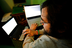 UK ENGLAND LONDON 13DEC10 - A masked member of the Anonymous group of hacktivists sits at home in front of computers...Actions credited to Anonymous are undertaken by unidentified individuals for, amongst other things, Distributed Denial of Service (DDos) attacks such as Operation Chanology in 2008 and Operation Payback in 2010...In December 2010 Operation Payback organisers (rumoured to be Anon Ops) focused their attention in DDoS attacks on websites of companies that oppose WikiLeaks...jre/Photo by Jiri Rezac..© Jiri Rezac 2010