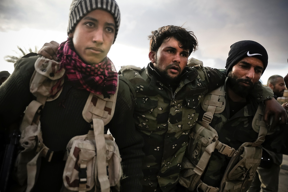Rebels carry an injured fighter to safety after taking heavy machine gun fire and artillery shelling during an air strike on Wednesday, March 9, 2011 while advancing between the oil port of Ras Lanuf and Bin Jiwad, Libya.  Medics working with opposition forces in eastern Libya are reporting over 400 rebels have been killed by pro-Qaddafi forces in the region since the uprise began.