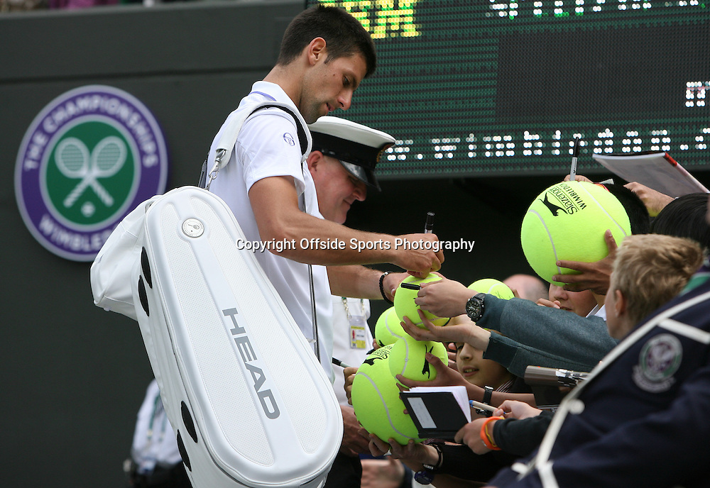 23/06/2011 - Wimbledon (Day 4) - Kevin Anderson vs. Novak Djokovic - Novak Djokovic signs autographs for fans on large tennis balls - Photo: Simon Stacpoole / Offside.
