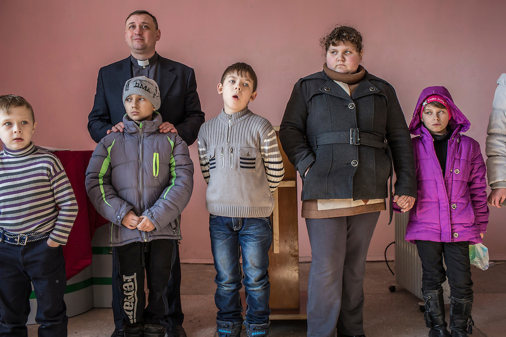 MARIINKA, UKRAINE - FEBRUARY 20, 2016:  Pastor Sergei Kosyak stands with children from his congregation during a service at the Christian Help Center of the Church of the Transfiguration in Mariinka, Ukraine. The Donetsk suburb has been the scene of some of the heaviest fighting recently between Ukrainian forces and pro-Russian rebels. CREDIT: Brendan Hoffman for The New York Times