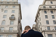 Seen from the rear, a man scratches with his ear beneath the tall architecture of office spaces above Green Park Underground station on Piccadilly, on 25th February 2020, in London, England.