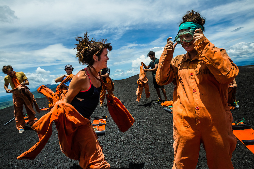 LEON, NICARAGUA - SEPTEMBER 18, 2014: Kirstyn McCasey, 23, (left) and Jade Cadoret, 20, tourists from Canada, gear up in orange jumpsuits and green goggles in preparation to board down Cerro Negro volcano. The jumpsuits are used for protective measures, because boarders reach high speeds of up to 95kilometers/hour and the rough surface at such high speeds can easily damage their skin. Guided tours are available from $29 USD to board down the volcano, located an hour outside of Leon. PHOTO: Meridith Kohut