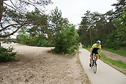 In Soest rijdt een man op een racefiets langs de Soesterduinen.<br /> <br /> In Soest a man is cycling on a road bike.