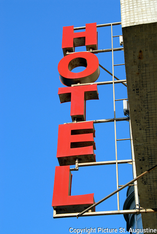 A Vertical Red HOTEL Sign Is Stand Out Against Bright Blue Sky The