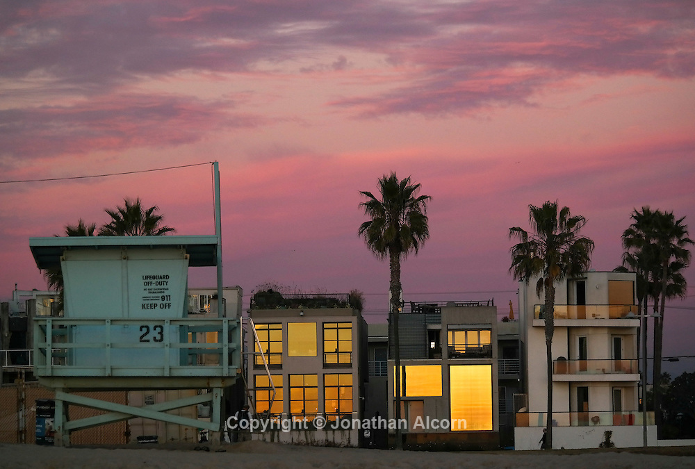 A lifeguard tower stands on the beach in front of beach houses in Venice Beach.