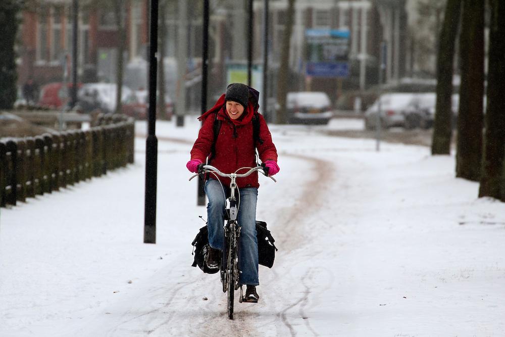 Een fietser rijdt op de Zijpendaalseweg in Arnhem door de sneeuw.<br /> <br /> A woman is cycling at the Zijpendaalseweg in Arnhem in the snow.