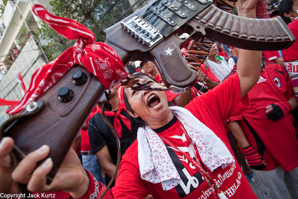 Apr. 12, 2010 - BANGKOK, THAILAND: Red Shirts hold up a guitar in the shape of an AK47 rifle in front of the Prime Minister's house on Soi 31 off of Sukhumvit Rd in Bangkok Monday. The funeral cortege for the Red Shirts killed in the violent crackdown Saturday wound through Bangkok and parts of the procession passed by the Prime Minister's home. Thousands of mourners came out to pay respects for dead Red Shirts. 21 people, including 16 Thai civilians were killed when soldiers tried to clear the Red Shirts' encampment in Bangkok. Thousands more came out to call for the government of Thai Prime Minister Abhisit Vejjajiva to step down. Today Gen. Anupong Paojinda, the Chief of Staff of the Thai Army, reiterated that the Army would not use violence to break up the protests and joined the call for the Prime Minister to call new elections. This is the beginning of Songkran, Thai New Year's week, and the government has cancelled the official festivities fearing more violence. It was during last year's Songkan festivities that the Thai Army and police used force to break up the Red Shirt protests. That protest is now called the Songkran Riots.         Photo By Jack Kurtz