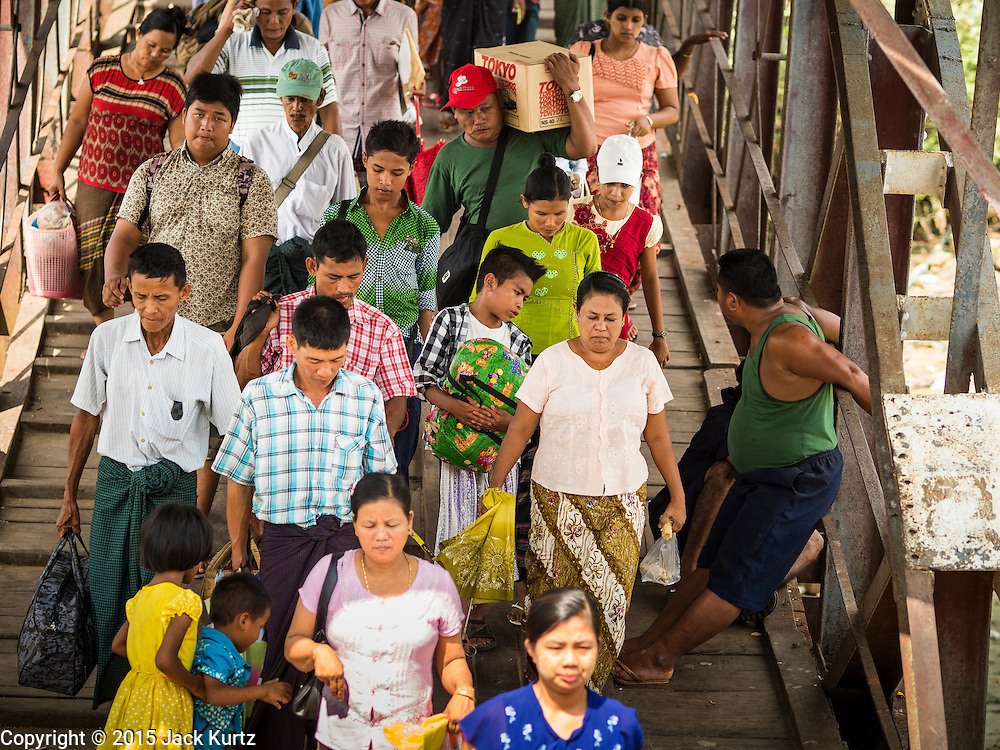 30 OCTOBER 2015 - YANGON, MYANMAR:  Passengers walk down to the Dala ferry in Yangon. The ferry to Dala runs continuously through the day between Yangon and Dala. Yangon, Myanmar (Rangoon, Burma). Yangon, with a population of over five million, continues to be the country's largest city and the most important commercial center.          PHOTO BY JACK KURTZ