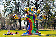 Roslyn, New York, U.S. - April 12, 2014 - During International Slow Art Day, visitors view Snake Tree, a mixed media outdoor sculptural installation 18' high, by Niki de Saint Phalle, and other artwork at the Nassau County Museum of Art on Long Island. During this annual worldwide event, those participating (not known if those shown are participants) went to local museums and viewed a small number of works of art, each for at least 10 minutes, and then discussed them afterward.