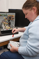 Woman with a mild learning disability working as a trainee computer technician, shown here attaching hard drive, helped into employment by the Ready 4 Work team, Nottinghamshire County Council