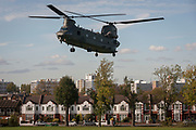 An army Chinook military helicopter takes off over Edwardian period homes line Finsen Road on Ruskin Park, on 25th October 2017, in south London, England.