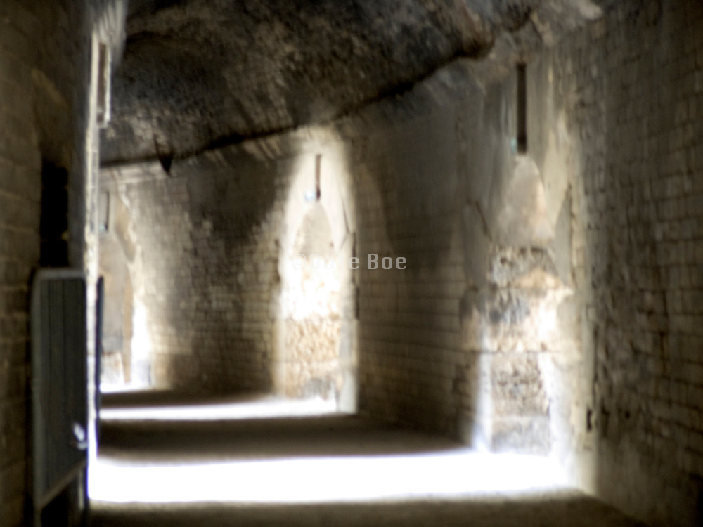 corridor with sun lighted arches Arles blurry