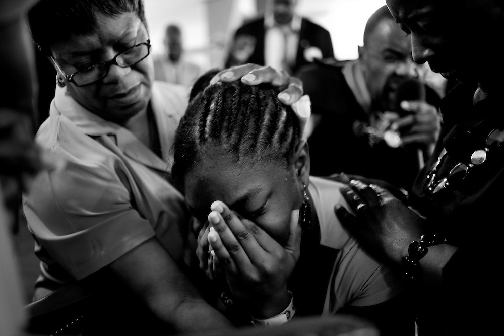 Rev. Warren Adkins, background, who has been a member of Macedonia Missionary Baptist Church for 58 years and its pastor for 36, sings The Lords Prayer over Kamora Johnson, 15, as she is held by members of the church, Alma Williams, left, and Barbara Denson during a Sunday service. Macedonia is Naples' oldest black church and is located in River Park. The church is central to many in the community and offers several youth programs for area kids.