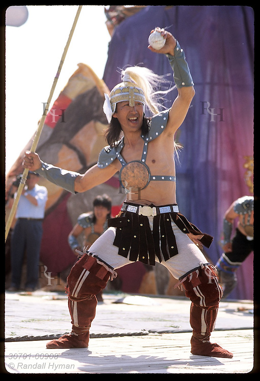 Costumed warrior dances on stage @ performance of ancient Olonkho epic of Ysyakh festival; Yakutsk Russia