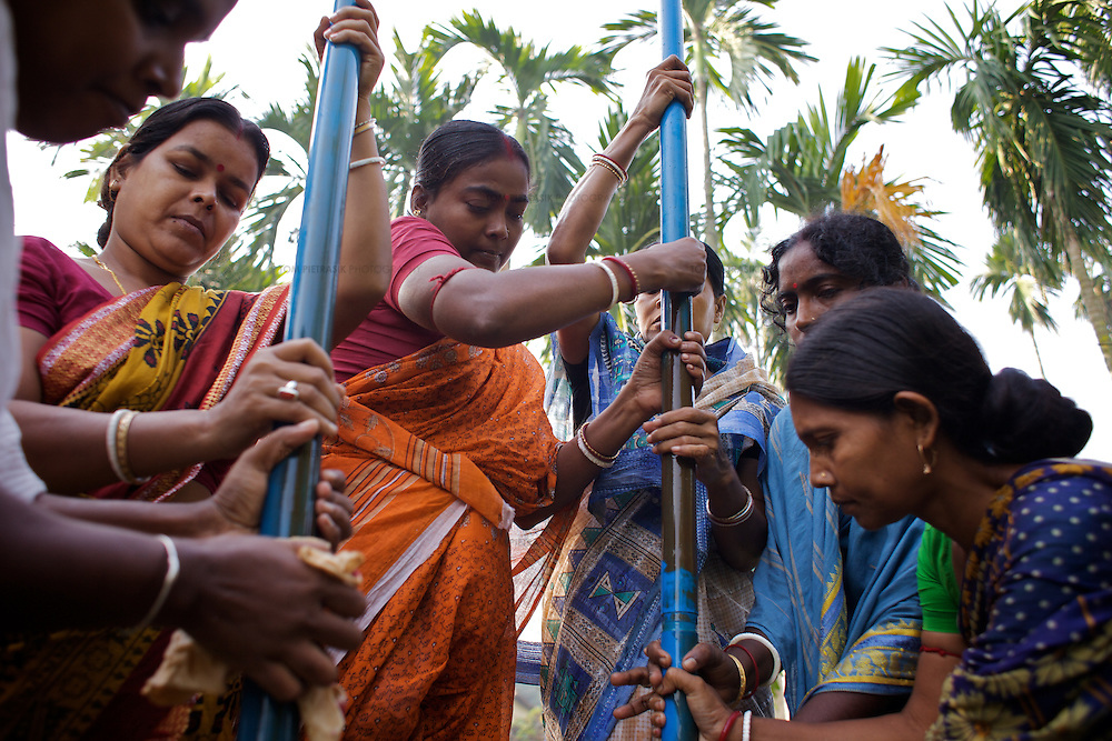 Women undertaking routine maintenance of the Lakhya village water pump. This pump was provided by the Government of West Bengal and is based on a design by UNICEF called TARA. The community is responsible for the monitoring of water quality and maintenance of the pump. The pump has a committee who fund quality control and maintenance by levying a charge of INR1 per month for each household that uses the pump. UNICEF through its partners the Ramakrishn Mission has provided training for local women so that they can undertake minor maintenance repairs to the pump and has also provided them the tools for this maintenance. The Ramakrishna Mission has provided TARA pump maintenance training for 143 groups in Purbamedinipur district. <br /> <br /> Photo: Tom Pietrasik<br /> Lakhya village, Purbamedinipur district, West Bengal. India<br /> October 25th 2009