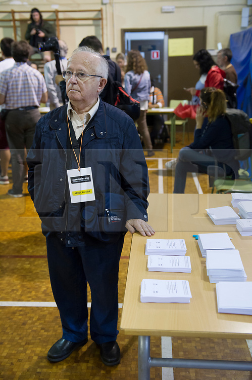 """© Licensed to London News Pictures. 01/10/2017. Barcelona, Spain.  <br /> <br /> A member of the organization keeping the ballots at Sedeta de Gracia´s Centre Civic poll station.<br /> <br /> Students, their parents, associations and neighbours have organized to carry out """"playful activities"""" during the weekend and keep open the Sedeta de Gracia´s Centre Civic.<br />  <br /> Since early in the morning dozens of people wait at the college´s door for the voting time under the rain.<br /> <br /> Mossos d´Escuadra said they won´t do nothing if that can destabilize social order.<br /> <br /> Catalonia is awaiting for today, October 1st, when the Spanish Region wants to vote in a self-determination referendum to get a independence.<br /> <br /> The Referendum´s Law was passed on last September 6th at the Catalonian Parliament thanks to the votes of """"Junts pel Sí"""" and """"CUP"""". Then it was suspended by the Spanish Constitutional Court, on next day.<br /> Carles Puigdemont, the President of the Government ofCatalonia, said he would ignore that and he and his Government will continue with the Referendum.<br /> <br /> The Spanish Government has sent to Catalonia thousands of """"Guardia Civil"""" and """"Policía Nacional"""" officers (two of the Spanish forces and state security forces), to enforce the ruling of the Constitutional Court and avoid the voting process on next Sunday. They will work with the Mossos d´Escuadra (the Autonomic police in Catalonia).<br /> <br /> To avoid the vote, the Spanish Government has prevented the opening of polling stations, some of which are schools.  <br /> <br /> Photo credit: Gustavo Valiente/LNP"""