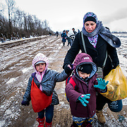 In subfreezing snowy weather, Syrian refugees walk the unoffical refugee crossing from the Tabanovce, Macedonia Train Station across the Serbian border.  A daily average of 2,200 refugees have crossed into Serbia throughout the winter. January 2016, near Miratovac, Serbia.