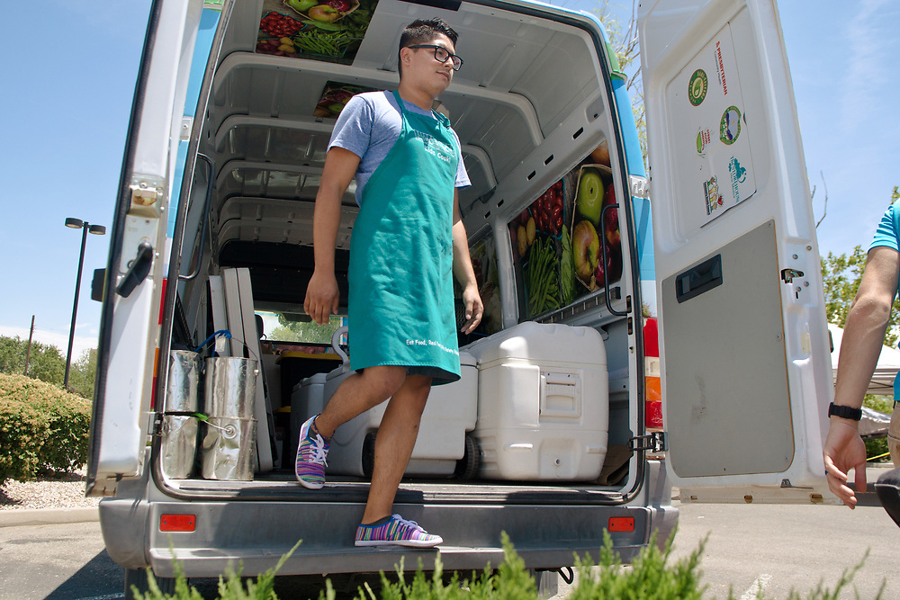 Manuel Davila, who works with Kids Cook, an education program, helps to load up the Mobile Farmers' Market from outside of Presbyterian Medical Group at 3436 Isleta Blvd. SW.  to get ready for their second market stop at First Choice Community Healthcare at 2001 El Centro Familiar Blvd. SW, Tuesday, June 6, 2017. (Marla Brose/Albuquerque Journal)