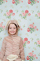 Portrait of young girl (5-6) in bunny costume against wallpaper with floral pattern