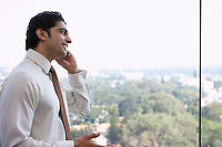 Business man using cell phone smiling side view
