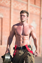 muscular shirtless fireman outdoors