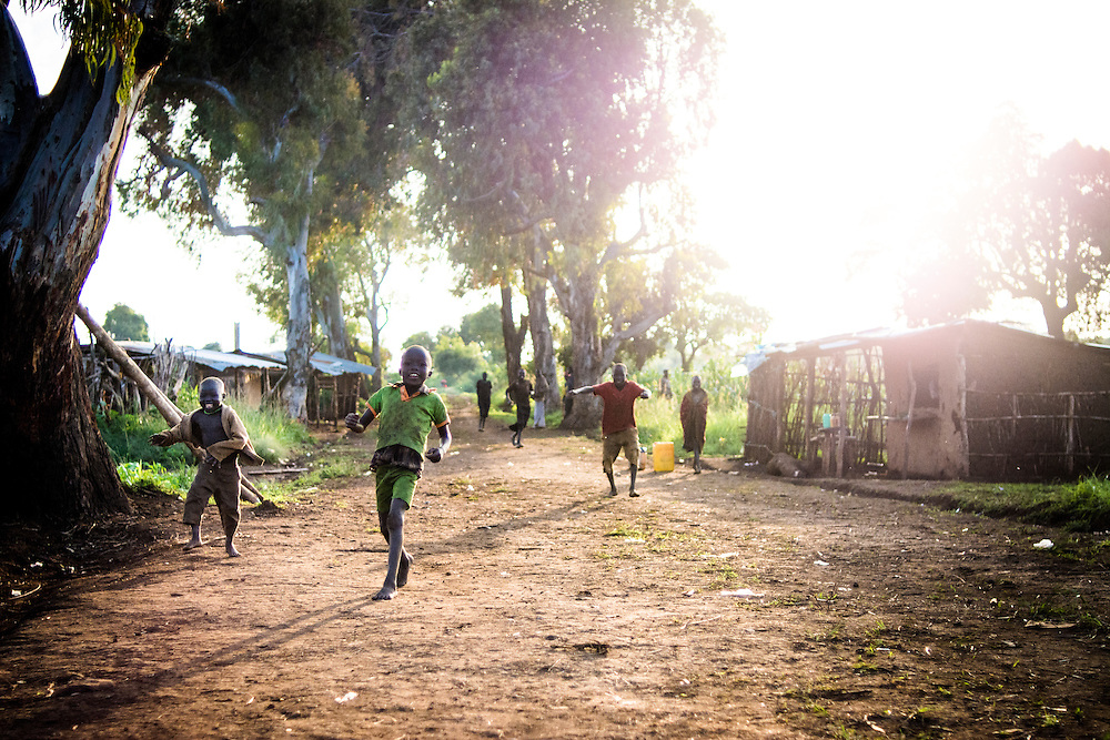 Kids run down the main street of Nagishot. Due to it's remote location, the village is highly self-sustainable and outside development hasn't overly influenced the area.