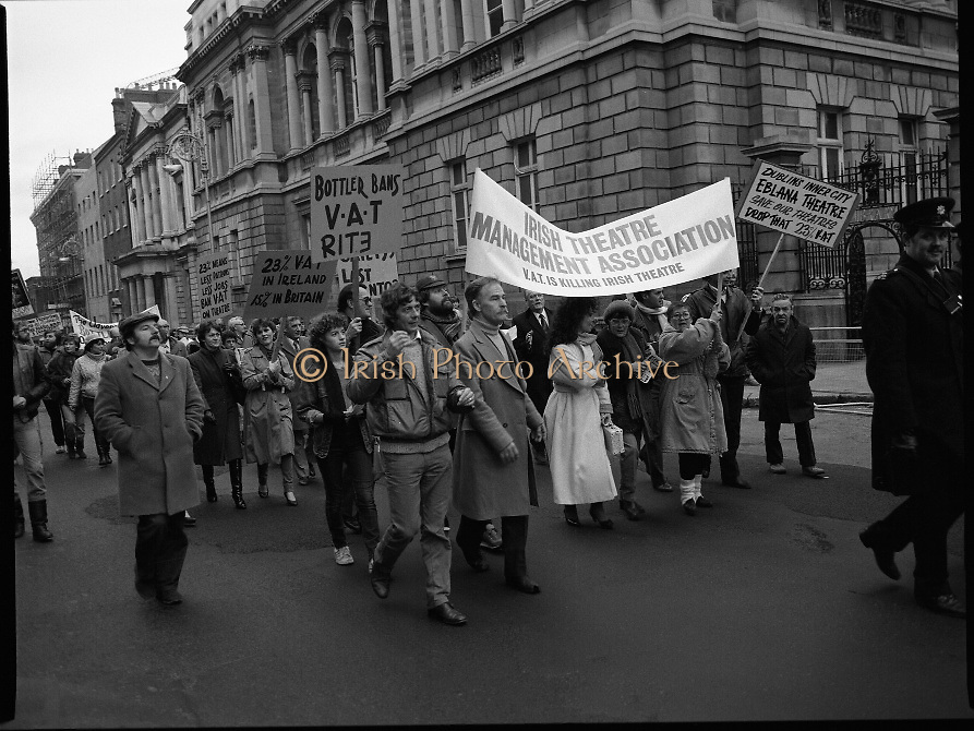 "Irish Theatre Industry Protest at Leinster House.1983.07.12.1983.12.07.1983.7th December 1983...With the imposition of a 23% V.A.T.rate on theatre tickets, the theatre industry was feeling the strain. Maureen Potter and Brendan Grace aka ""Bottler"" led the protest to the gates of Leinster House Dublin.. .Picture of Maureen,carrying banner,and her theatre colleagues lead the protest up Kildare St,Dublin to the Dail."