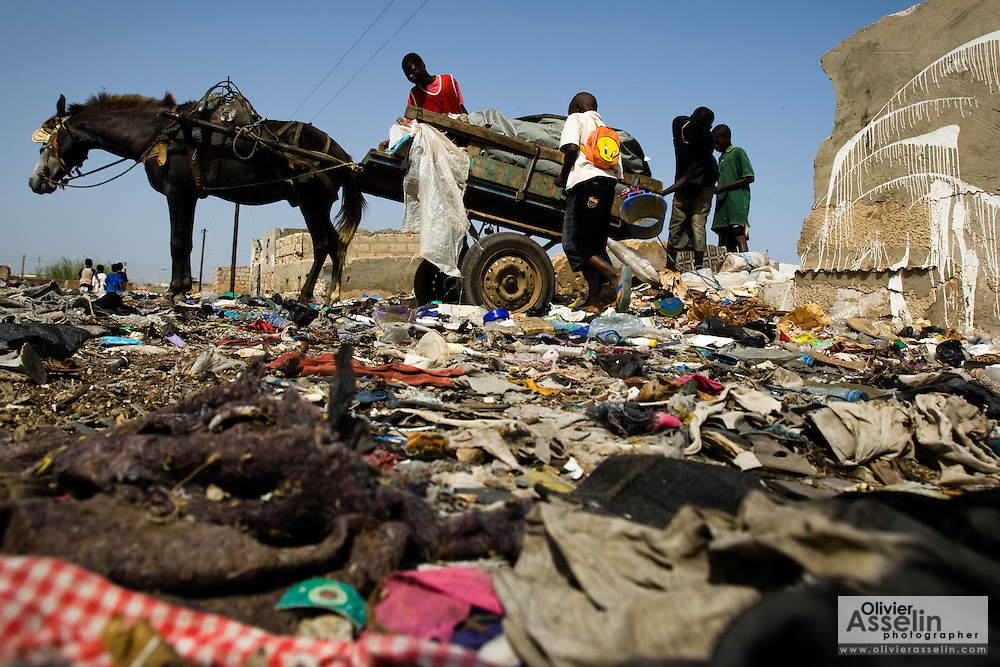 Boys unload a horse-pulled cart loaded with garbage into a home that was damaged by flooding in the Medina Gounass neighborhood of Guediawaye, Senegal on  Friday May 1, 2009. (Olivier Asselin for the New York Times).