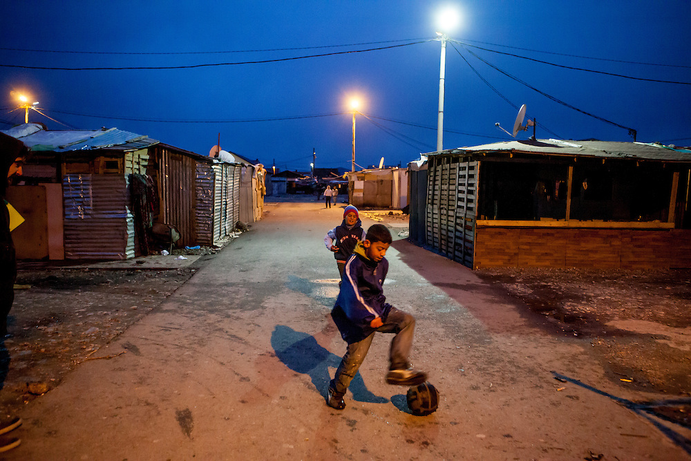 Children palying footbal in the area with new and old housing facilities at Konik Camp located in the suburbs of the city of Podgorica, Montenegro. A huge fire in 2012 detroyed a big part of the refugee camp and many of the inhabitants are living now in containers.