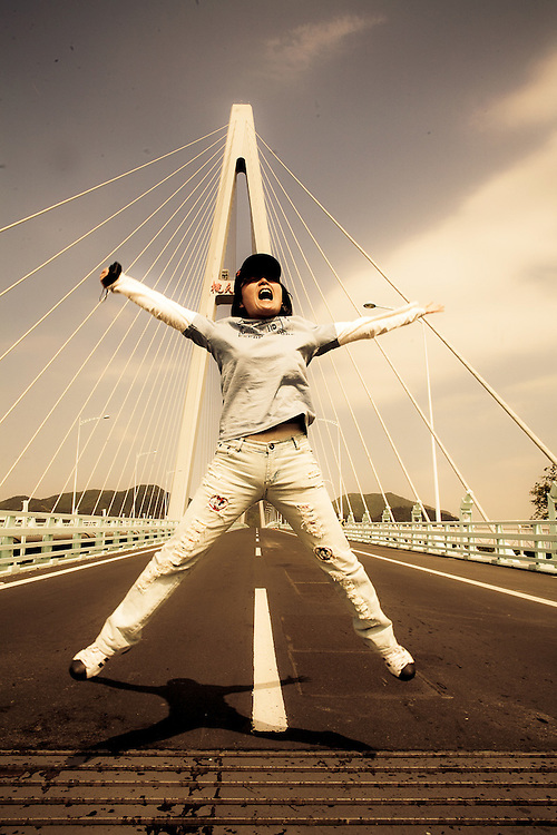 young Chinese girl leaping for joy on new bridge,Zhoushan
