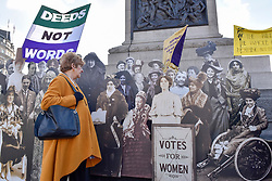"""© Licensed to London News Pictures. 06/02/2018. LONDON, UK.  Angela Stern from London poses against a pop-up exhibition featuring 59 life-sized images of campaigners, along with famous rallying slogans such as """"deeds not words"""" in Trafalgar Square marking 100 years since the Representation of the People Act was passed, granting some women over the 30 in the UK the right to vote for the first time.  Photo credit: Stephen Chung/LNP"""