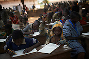 Boys draw during a class at the Christian IDP camp at the Bishop's residence in the town of Bossangoa December 19, 2013. Many of the images they produce depict violent scenes witnessed including massacres by Seleka fighters on civilians and the Christian anti-Balaka. UNHCR is distributing 3000 Non Food Items (NDIs) to those in need. There are 35,500 IDPs sheltering at the residence of the Bishop and another 5000 sheltered between the home of the Imam and a local school. Many fled their homes in September when violent attacks broke out between anti-Balaka fighters and Seleka rebels. On Thursday 5th December Christian anti-Balaka militants entered the city and attacked Seleka rebels. 18 civilians were killed in Bossangoa during these attacks. The Seleka made up of a Muslim majority with many of the rebels originating from northern Central African Republic, Sudan and Chad brought to power a new president Michel Djotodia, a former Seleka leader in a March 24, 2013 coup.  The political establishment has failed to control the armed group that has wreaked havoc, including murdering, looting and burning of villages on the civilian population with mass displacements resulting.UNHCR / S. Phelps / December 2013