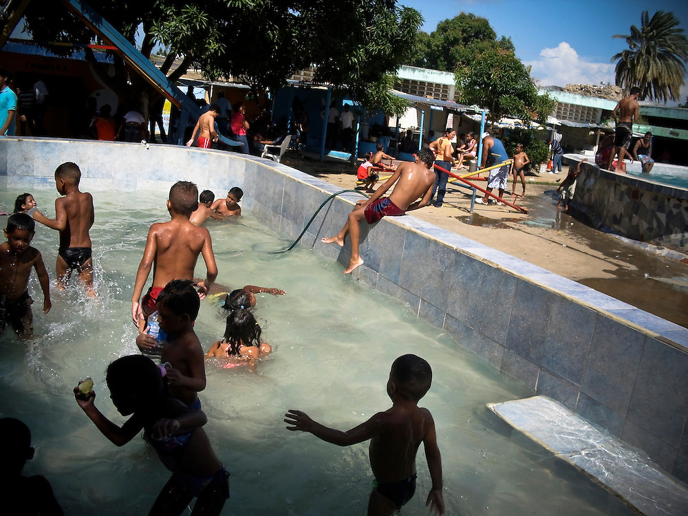 """Visiting children swim inside San Antonio prison in Porlamar, Venezuela.  The prison on Margarita Island houses 2,000 inmates, and is known amongst criminals as the prime place to serve time.  It is unofficially run by convicted drug trafficker, Teófilo Rodríguez, who said in an interview that his goal was to create an atmosphere inside the prison as a, """"peaceful party"""".  During his reign at the prison, Rodríguez has constructed four swimming pools, a cockfighting arena, hosts hip hop concerts and dances at the prison discothèque, and has built over 200 private rooms where prisoners may enjoy conjugal visits three times a week.  """"There are kids who don't have the means to go to a water park, they don't have the money to go to a swimming pool. They come here and they live their dream"""" Rodríguez said."""