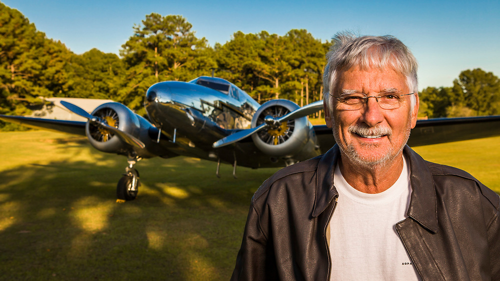 "Joe Shepherd, a retired Northwest Airlines pilot.  In the background is his completely restored and airworthy Lockheed 12-A Electra Junior, one of the few still flying.  Joe (in a dress and wig!) and his aircraft appeared in the motion picture ""Amelia""."