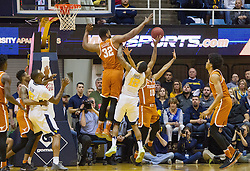 Feb 20, 2017; Morgantown, WV, USA; Texas Longhorns forward Shaquille Cleare (32) blocks a shot by West Virginia Mountaineers guard Tarik Phillip (12) during the first half at WVU Coliseum. Mandatory Credit: Ben Queen-USA TODAY Sports