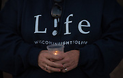 A pro-life vigil participant holds a candle during a 40 Days for Life event in Green Bay. (Photo by Sam Lucero)