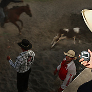 SAN CARLOS, PANAMA - FEBRUARY 11: A judge uses a stopwatch as a timer as cowboys compete in a lasso competition in San Carlos, near Boquete, Panama, on February 11, 2007. In the competition, each heat features one town's team versus another in a tournament bracket style. The speed of the calf's capture determines points.  (Photo by Logan Mock-Bunting)