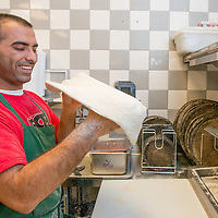 Mansoor Zameer tosses a pizza dough at First Class Pizza on Riverwalk Parkway in Riverside, Aug. 28, 2014.  (Eric Reed/Redlands Magazine)