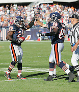 CHICAGO - OCTOBER 16:  Running back Thomas Jones #20 of the Chicago Bears celebrates with teammates with a high five after scoring the second of of two rushing touchdowns against the Minnesota Vikings at Soldier Field on October 16, 2005 in Chicago, Illinois. The Bears defeated the Vikings 28-3. ©Paul Anthony Spinelli *** Local Caption *** Thomas Jones