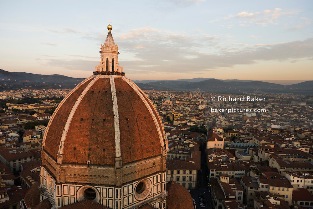 Tourists stand on a narrow platform near the top of Brunelleschi's Dome, seen from the adjecent Giotto's Bell Tower (campanile) in Florence. The Basilica di Santa Maria del Fiore is the cathedral church (Duomo) begun in 1296 in the Gothic style to the design of Arnolfo di Cambio and completed structurally in 1436 with the dome engineered by Filippo Brunelleschi. The exterior of the basilica is faced with polychrome marble panels in various shades of green and pink bordered by white and has an elaborate 19th century Gothic Revival facade by Emilio De Fabris. The cathedral complex, located in Piazza del Duomo, includes the Baptistery and Giotto's Campanile. The three buildings are part of the UNESCO World Heritage Site