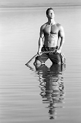 sexy man in a lake holding an enormous rope