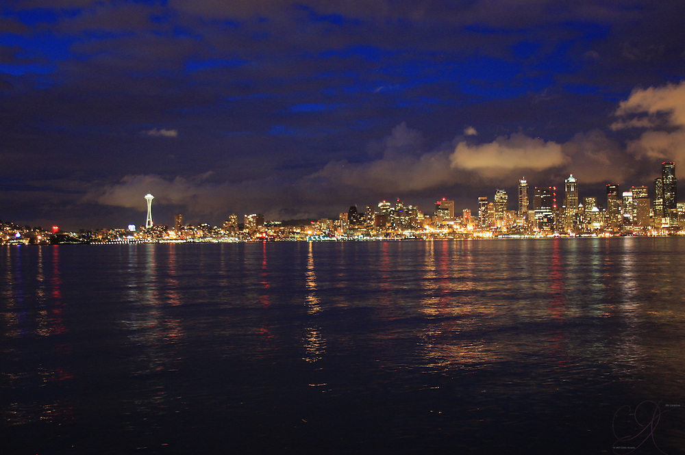 The Seattle skyline from West Seattle.<br /> <br /> The city lights shimmer upon the sound as the clouds roll down to building-top level, illuminated by the city lights.