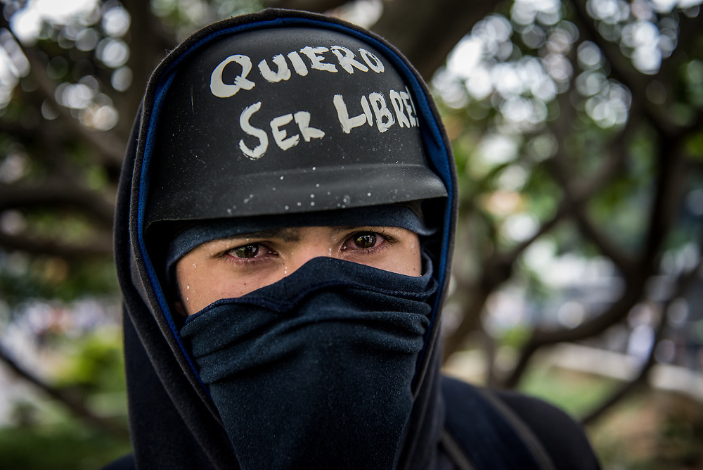 "CARACAS, VENEZUELA - MAY 8, 2017:  An anti-government protester, eyes read after being heavily tear gassed, poses for a portrait wearing his helmet that says, ""I want to be free"", during clashes with security forces. The streets of Caracas and other cities across Venezuela have been filled with tens of thousands of demonstrators for nearly 100 days of massive protests, held since April 1st. Protesters are enraged at the government for becoming an increasingly repressive, authoritarian regime that has delayed elections, used armed government loyalist to threaten dissidents, called for the Constitution to be re-written to favor them, jailed and tortured protesters and members of the political opposition, and whose corruption and failed economic policy has caused the current economic crisis that has led to widespread food and medicine shortages across the country.  Independent local media report nearly 100 people have been killed during protests and protest-related riots and looting.  The government currently only officially reports 75 deaths.  Over 2,000 people have been injured, and over 3,000 protesters have been detained by authorities.  PHOTO: Meridith Kohut"