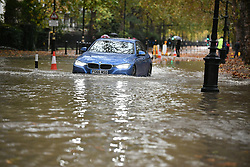 © Licensed to London News Pictures. 24/10/2019. London, UK. Traffic passes through heavy surface water on the roads near St James's Park in Westminster after a heavy downpour of rain. Photo credit: Ben Cawthra/LNP